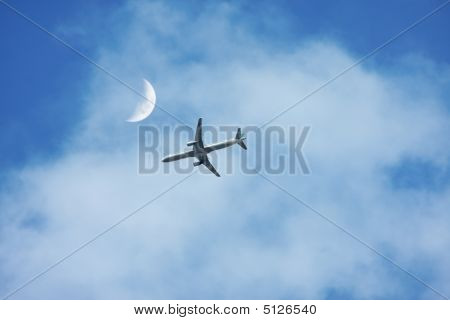 an airplane flyiing near the moon on a cloudy sky poster