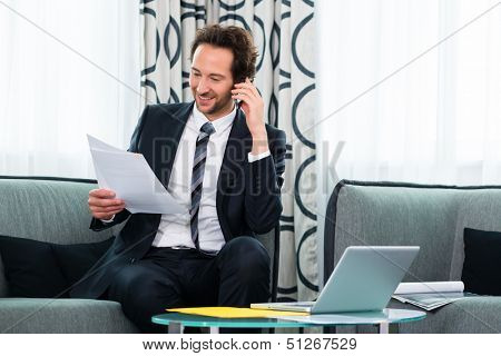 Businessman working in business hotel, he discusses some documents with a customer on the phone