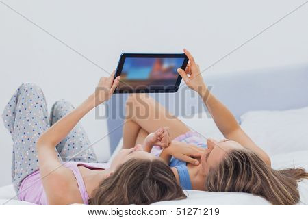Friends wearing pajamas holding tablet in bed