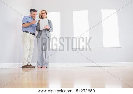 Cheerful blonde realtor showing an empty room and some documents to a potential attentive mature buyer