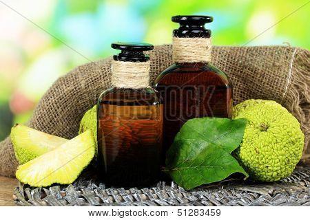 Osage Orange fruits (Maclura pomifera) and medicine bottles, on wooden table, on nature background