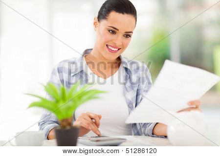 young woman paying her bills at home