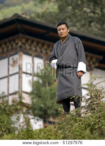 Bhutan - October 2010: Traditional Tourist Guide In Front Of A Typical Bhutanese House Wearing His N