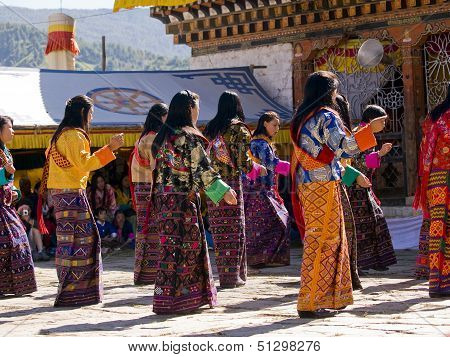 Jakar, Bhutan - October 24, 2010: Women Wearing Traditional Kira Dresses Dancing At The Jakar Tsechu