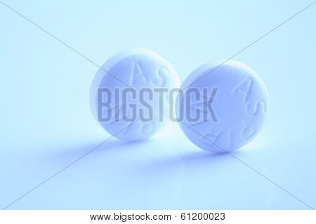 Two circular aspirin pills on blue background