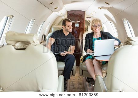 Business colleagues with laptop and digital tablet discussing on private jet