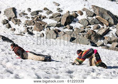 Mt Kailash, Tibet, China - May 26, 2012: Buddhist woman pilgrims making the kora (circumambulation) around Mt. Kailash and performing full body prostrations