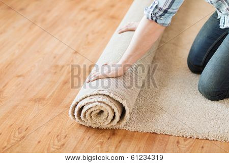repair, building and home concept - close up of male hands unrolling carpet
