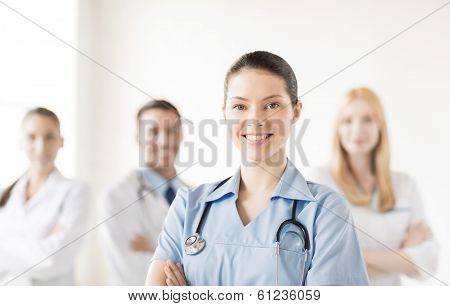 attractive female doctor or nurse in front of medical group