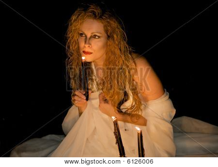 Attractive Woman Blowing Out A Candle.