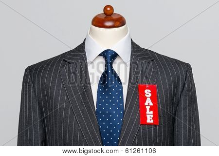 Front view of a Mens grey wool pinstripe suit jacket with blue tie and white shirt on a tailors dummy, sale price tag hanging from the button hole.