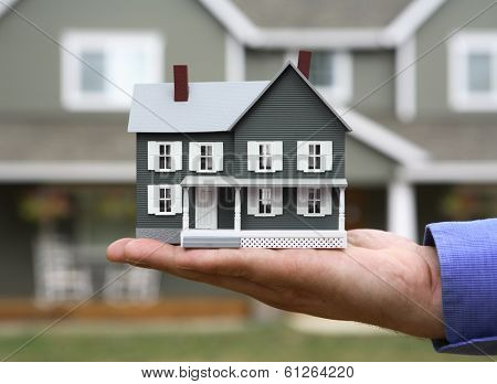 miniature house in man's hand with house in background