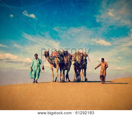 Vintage retro hipster style travel image Rajasthan travel background - two Indian cameleers (camel drivers) with camels in dunes of Thar desert Jaisalmer, Rajasthan, India with grunge texture overlaid