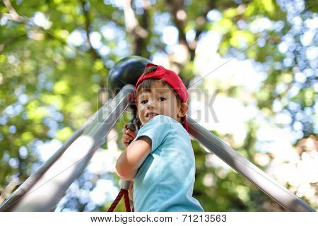 Little Boy At Top Of Jungle Gym