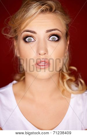 Beautiful young blond woman with a horrified expression looking at the camera with her eyes wide open in shock