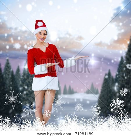 Pretty santa girl presenting with hands against snowy landscape with fir trees poster