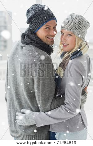 Cute couple in warm clothing hugging smiling at camera against snow falling