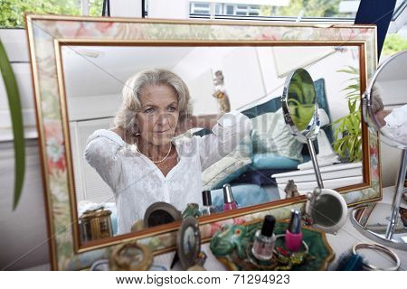 Mirror reflection of senior woman putting on necklace at home