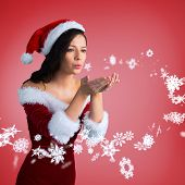 Pretty girl in santa outfit blowing against red vignette poster