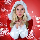 Pretty girl in santa outfit blowing against red snow flake pattern design poster