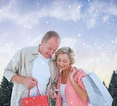 Couple with shopping bags and smartphone against snowy landscape with fir trees poster