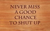 Never miss a good chance to shut up - an old saying on wooden red oak background poster