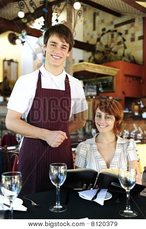 Waiter And Happy Costumer At The Restaurant