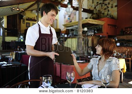 Waiter Giving Menu To Costumer At The Restaurant