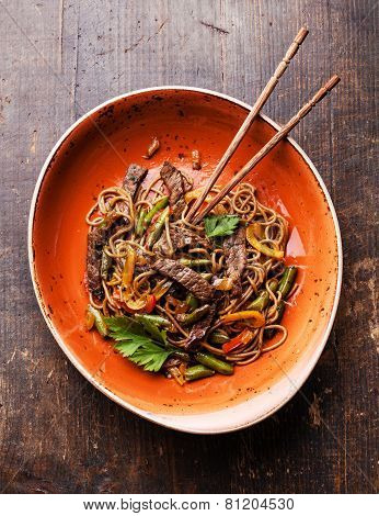 Fried noodles Yakisoba with beef on red plate poster