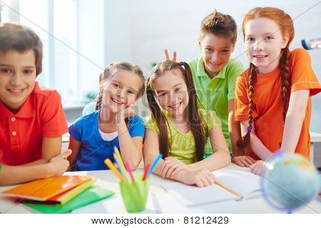 Group of little friendly schoolmates looking at camera