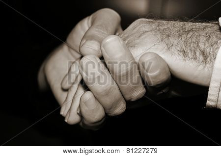 closeup of a young man holding the hand of an old man, in black and white
