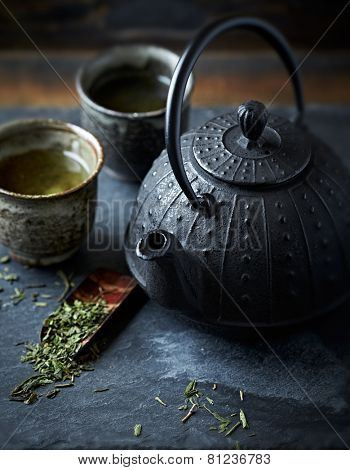 A cast iron tea pot and green tea in ceramic cups