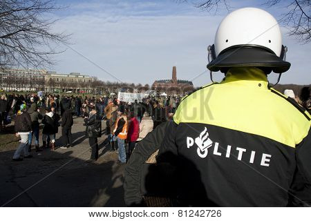 Police Officer Watching Protesters on the Malieveld in the Hague Holland