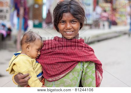 young wom?n in traditional clothing carrying a child in Manali old Market .