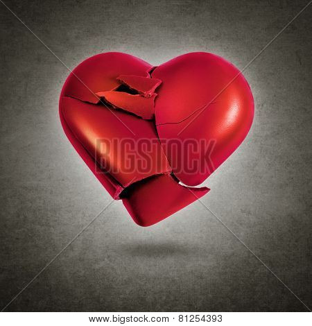 Broken red heart hovering over a gray textured background