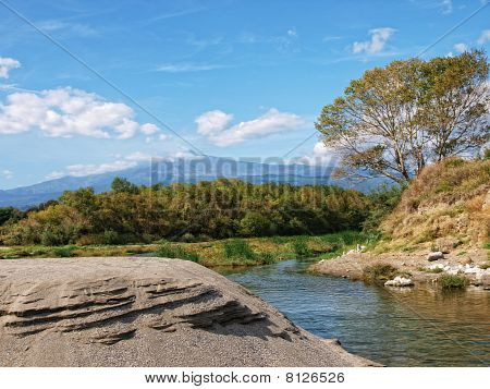 River with background of the volcano Etna