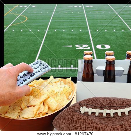 Closeup of a man's hand holding a TV remote with a bowl of chips and a six pack of beer with a deflated football. The TV screen has a football field with remote pointed at the screen.