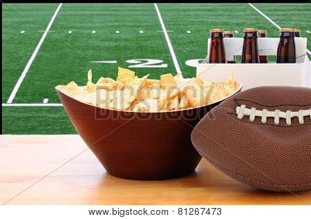 A deflated football and Six Pack of Beer and bowl of chips on a table in front of a big screen TV with a Football field. Great for Super Bowl themed projects. Horizontal format.
