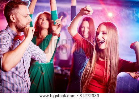 Happy young couple and their friends on background dancing together in night club