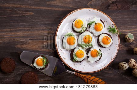 Preparation quail egg canapes with pumpernickel bread for Easter