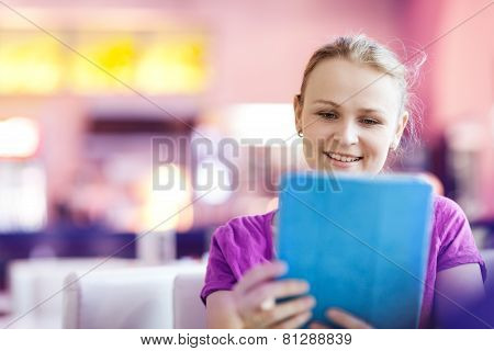 Woman using tablet PC in the restaurant indoors