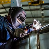 Man welding with reflection of sparks on visor. Hard job. Construction and manufacturing poster