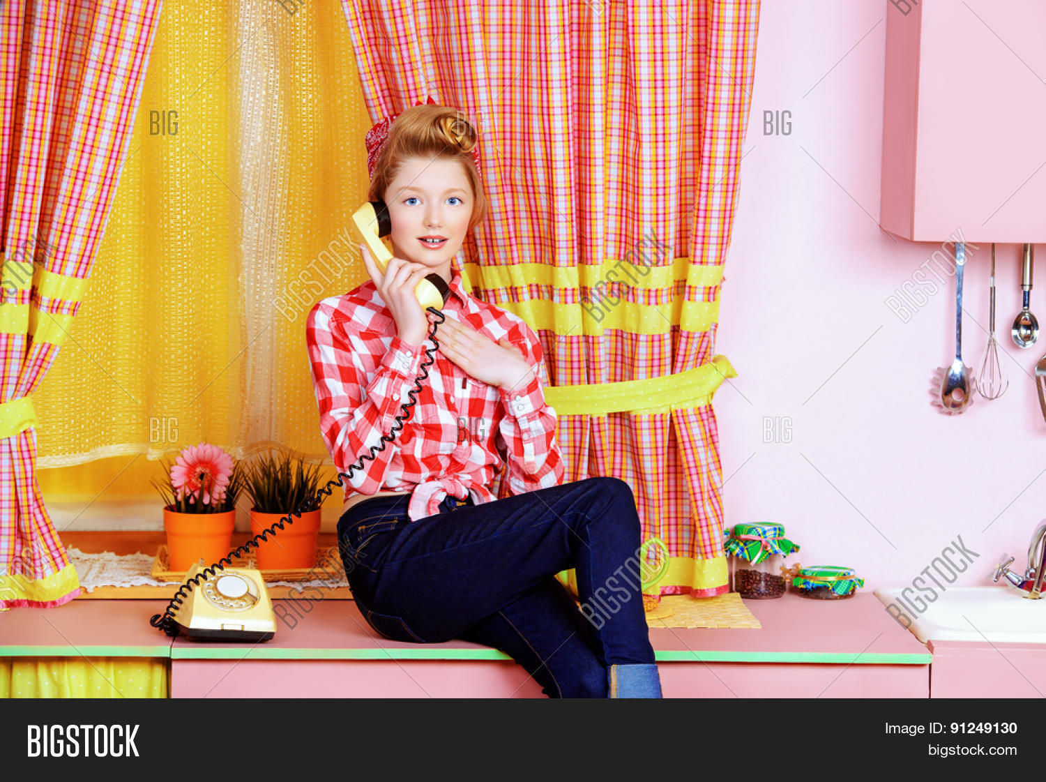 05369968b4c3 Pretty teen girl talking on the phone on a pink kitchen. Beauty