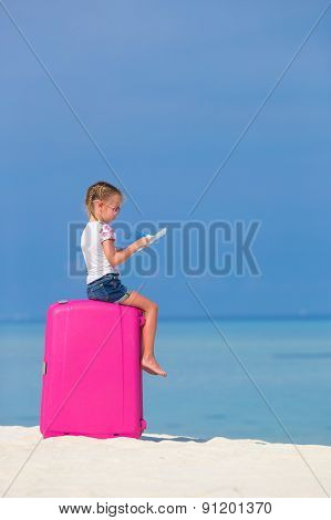 Little adorable girl with big pink suitcase and map of island on white beach