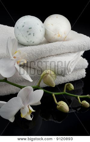 White bath balls with towels and white orchid on black bacground poster
