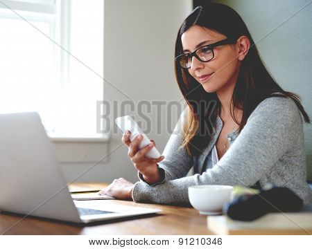 Woman Sitting In Home Office Checking Mobile Phone.
