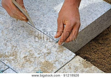 Worker Creates Close Jointing Between Paver Blocks