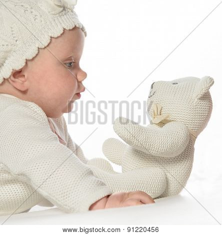baby girl child lying down on white blanket  fashion portrait  studio shot isolated on white caucasian playing with white teddy bear in hat