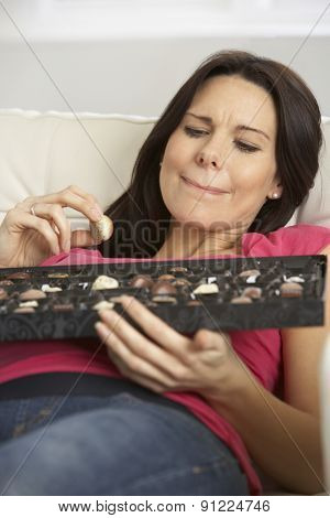 Pregnant Woman Eating Box Of Chocolates Sitting On Sofa At Home