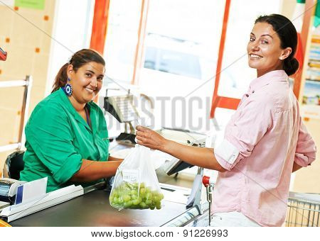 Customer buying food at supermarket and making check out with cashdesk cashier teller worker in store